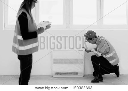 Maintenance Engineer checking air conditioner, black and white