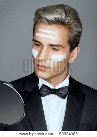 Classy gentleman looking in the mirror. Well-groomed man applying wrinkle cream or anti-aging skin care cream. Beauty & Skin care concept.