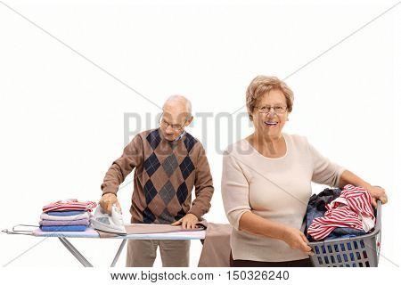Joyful mature woman holding a laundry basket and a mature man ironing isolated on white background