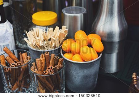Making mulled wine for sale at country fair. Glintwine accesories, stirring wooden sticks, spices and citrus, cinnamon sticks and kumquat in metal bowls closeup.