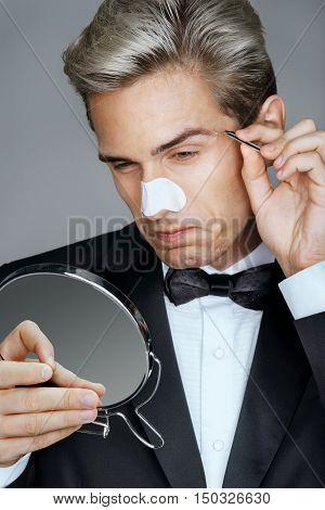 Man looking in the mirror wincing in pain while plucking his eyebrows. Photo of elegant man applying clear-up strips on nose for remove blackheads. Beauty & Skin care concept.