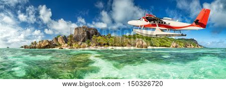 Beautiful Seychelles tropical beach Anse Source D Argent at La Digue island with flying seaplane
