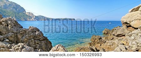 Bay Panorama With Blue Ocean, Rocks And Mountains