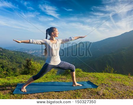 Yoga outdoors - sporty fit woman doing yoga asana Virabhadrasana 2 - Warrior pose posture outdoors in Himalayas mountains in the morning