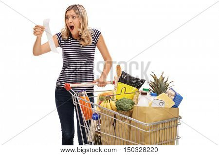 Shocked young woman looking at a store receipt isolated on white background