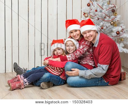 big family in red santa hats near the faux christmas tree in studio