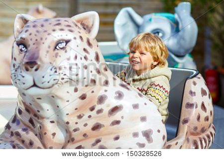 Funny little kid boy riding on animal on roundabout carousel in amusement park. Happy toddler having fun outdoors on sunny day.