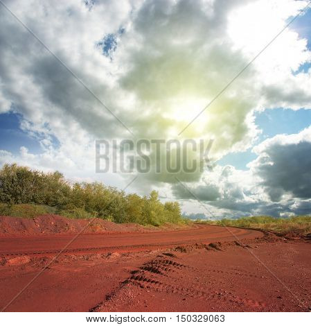 landscape with road on red ground and cloudy sky in Krivyi Rih, Ukraine