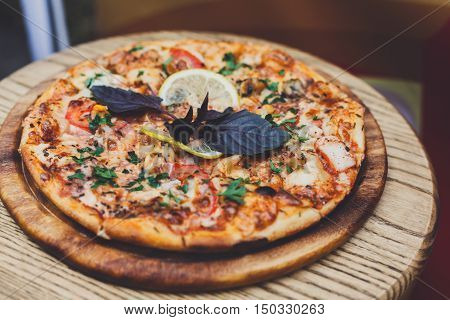 Delicious italian pizza with pepperoni, chicken ham, corns and black olives - thin pastry crust at wooden desk. Pizza served outdoors by vendor on country fair picnic party, closeup of tasty snack.
