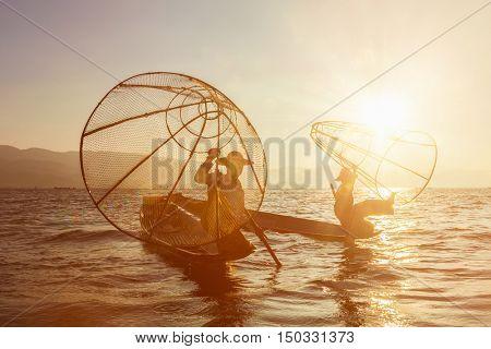 Myanmar travel attraction landmark - two traditional Burmese fishermen at Inle lake, Myanmar famous for their distinctive one legged rowing style on sunrise sunset