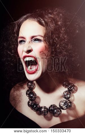 Vintage style portrait of young beautiful woman with gothic Halloween make-up and black scleral lenses