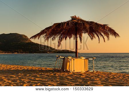 Vintage photo of chair and umbrella on the beach at sunset in Greece