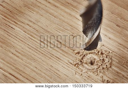 old drill bit drilling hole in wooden plank
