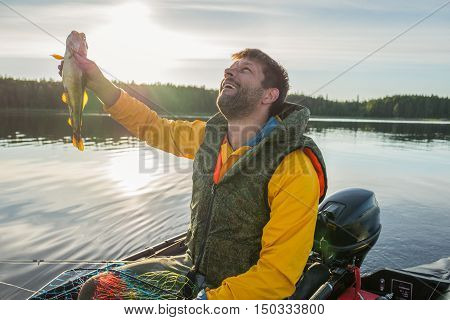 Handsome fisherman catched a haddock and looking to the sky