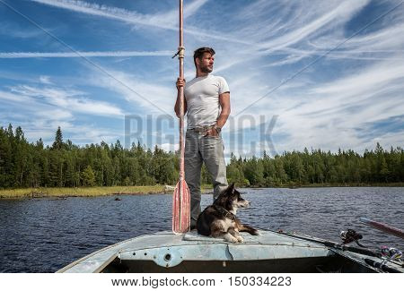 Handsome man is standing on the boat with baddle in his hands and dog near of his legs