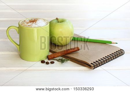 set of frothy cappuccino with cinnamon and apple notebook pencil / working environment in shades of green