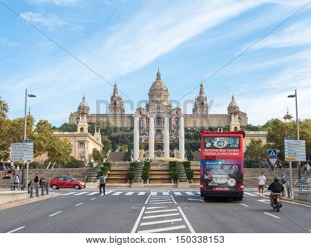 Barcelona - 10 October 2015: The road to the National Museum of Catalonia the tourist bus travels and people walk October 10 2015 Barcelona Spain