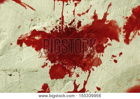 Red blood splatter on a grunge wall.
