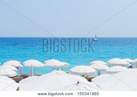 turquiose water of cote dAzur over white beach umbrellas, France