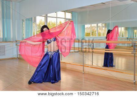 Beautiful woman dancing in arabic dance costume, oriental or belly dance.