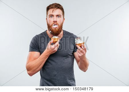 Filthy bearded young man eating cream cakes isolated on white background
