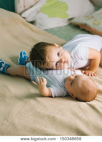 Small baby boy lying on bed in blue bootees and his brother in striped pajamas put his head on his tummy