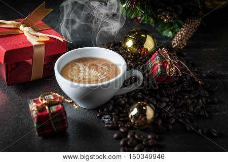 Coffee cup and christmas toys with pine brench on black stone background .