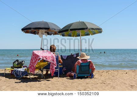 Two bathers enjoy the sandy beach to stay under the umbrella