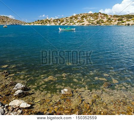 Traditional fishing boat on azure crystal clear sea water in the bay of Simi island, Greece