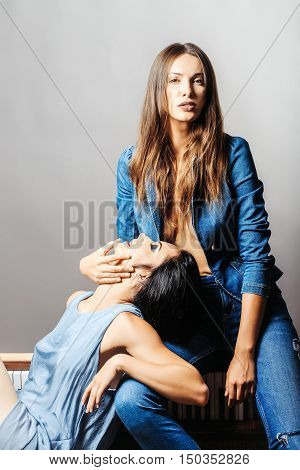 Sexy brunette girl with unbuttoned denim shirt holds beautiful woman with short black hair