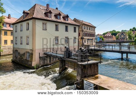 Bamberg Germany - May 22 2016: Dams bridges old houses on artificial islands and banks of the Regnitz river. Historic city center of Bamberg is a listed UNESCO world heritage site.