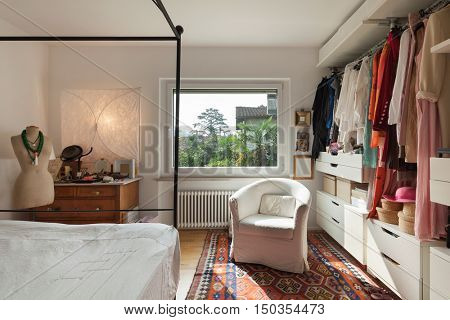 Interior, comfortable bedroom with wardrobe and armchair