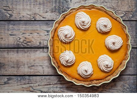 Festive Homemade Delicious Pumpkin pie with whipped cream and spices made for Thanksgiving and halloween, top view.