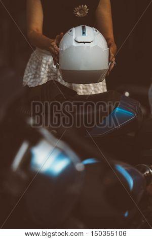 Unrecognizable woman putting white modern helmet on bike seat