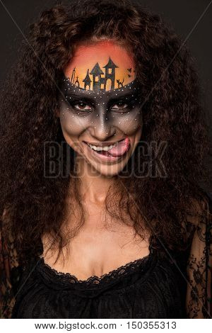 Halloween devil's bride. Portrait of young woman in dark artistic image with scary makeup veil and terrible picture on her forehead.