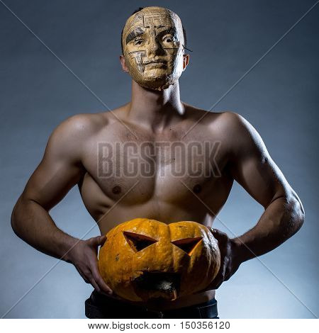 Muscular Man In Mask With Pumpkin