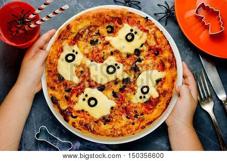 Child cooking pizza on Halloween. Funny ghost pizza with sausage cheese and olives top view