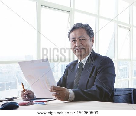 portrait of senior asian 60s years old working on office table happy face