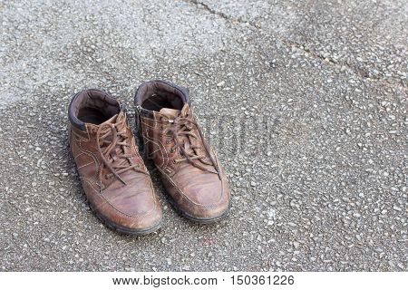 Old brown leather shoes on cement floor. Pair of old dirty brown leather shoes.