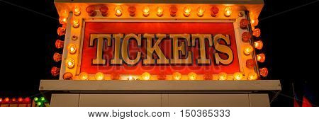 Glow of a neon ticket sign at a fair