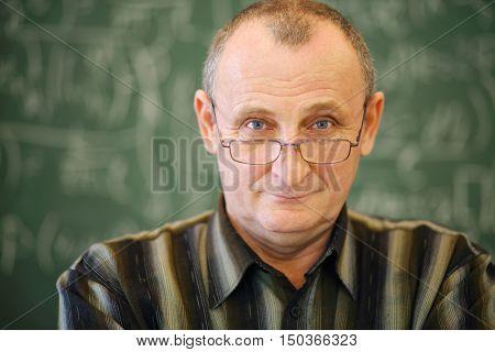 Old teacher in glasses stands near blackboard in school classroom, shallow dof