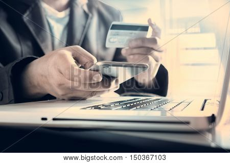 Online payment, Man's hands holding a credit card and using smart phone for online shopping