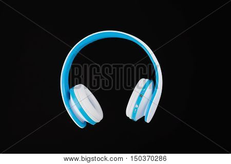 Blue wireless headphones isolated on black background