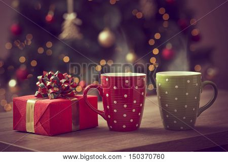 Nicely wrapped gift box and two cups of hot coffee set on the coffee table with the decorated Christmas tree in the background