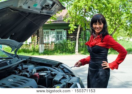 Attractive smiling business woman near car with an open cowl