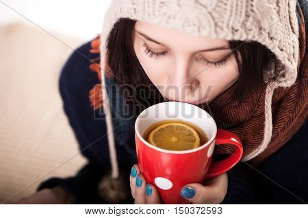 Woman enjoying a large cup of freshly brewed hot tea as she relaxes on a sofa in the living room.