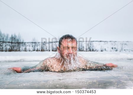 Man swimming in the winter ice hole