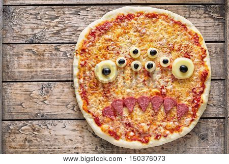 Halloween creative scary food monster zombie face with eyes pizza snack with mozzarella and sausage on vintage wooden table background. Traditional holiday celebration party decoration recipe