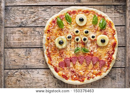 Halloween creative scary food eye monster zombie face pizza snack with mozzarella, basil and sausage on vintage wooden table background. Traditional holiday celebration party decoration recipe