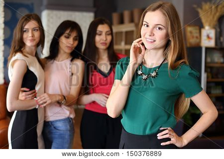 Young beautiful woman poses in cafe and three girls apprising look out of focus